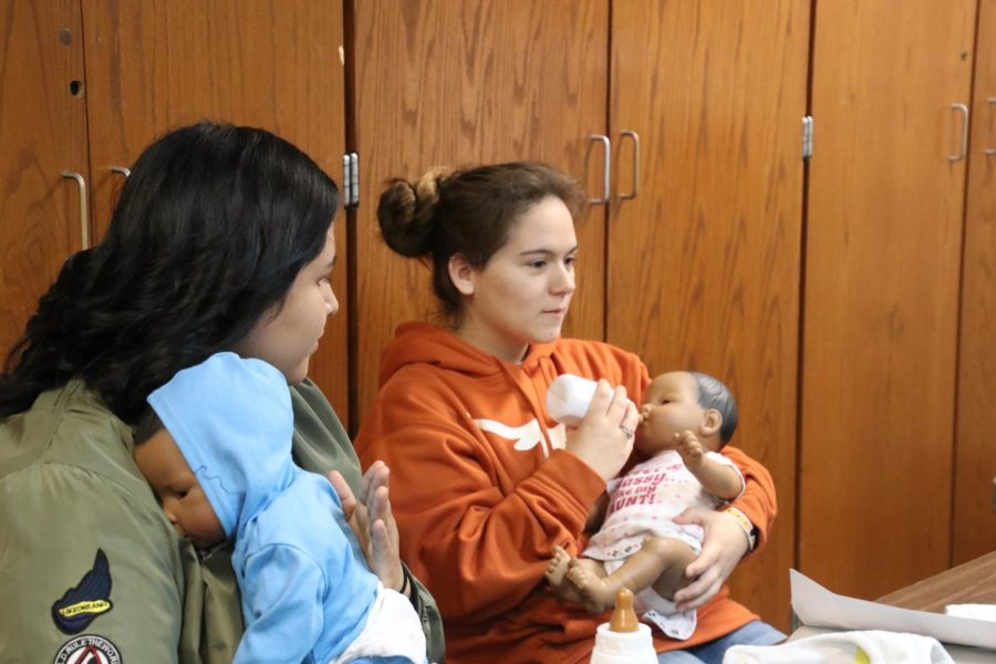 Sabrina Gaines and Billie Cajero practice taking care of babies