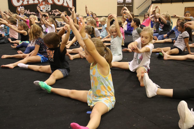 Kids stretching at mini cheer camp.