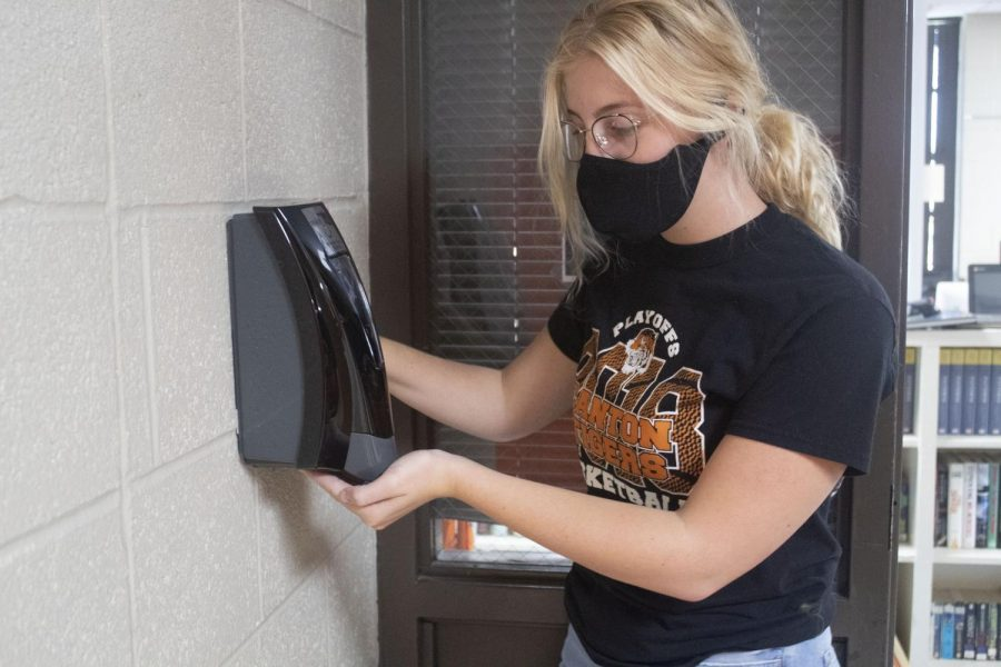 Kenzi Nix shows her new daily routine outside of Mrs.Barney's classroom. The school provided hand sanitizer stations and water bottle filling stations to help prevent the spread of Covid-19.