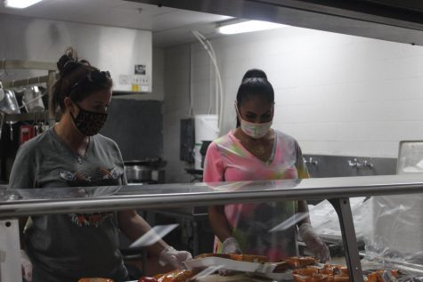 Melina Foster and Katrina Kopf prepare lunches. The lunches were for elementary.