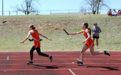 Junior Madison Rauh hands the baton to junior Hopelin Hood in their mile relay.