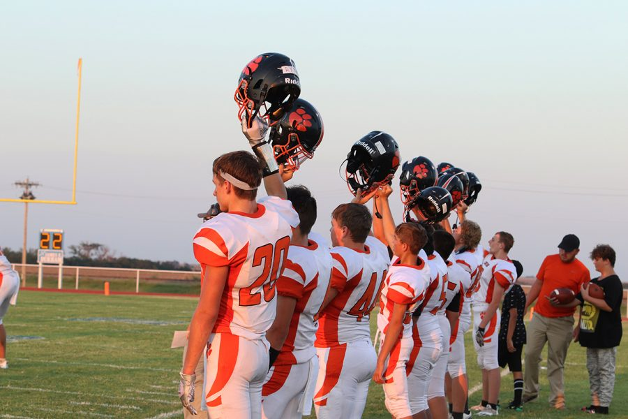 A line of Canton Tigers hold their helmets for kickoff.